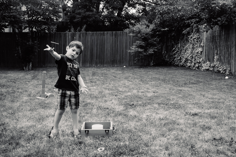 boy plays yard game - Documentary Family Photography