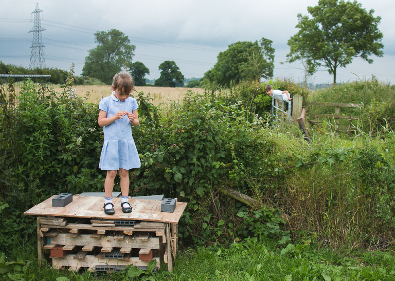 girl standing on palettes in field - Documentary Family Photography