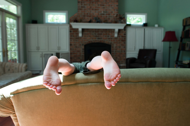 child's feet over couch - Documentary Family Photography