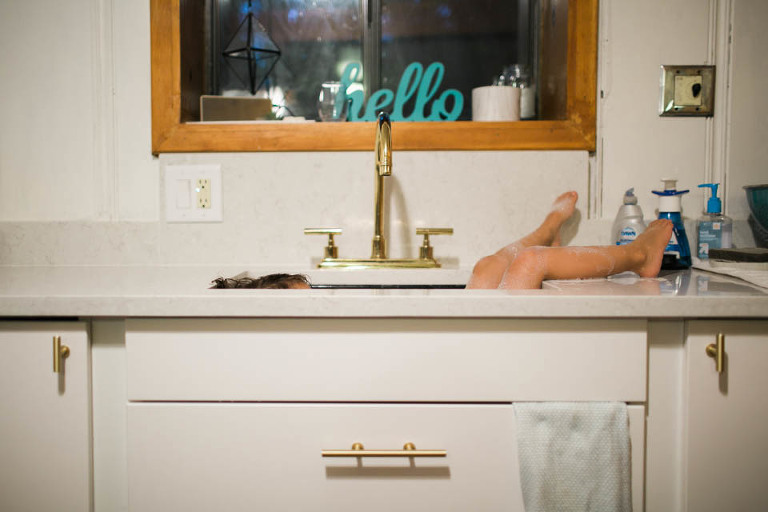 girl lounging in kitchen sink - Documentary Family Photography