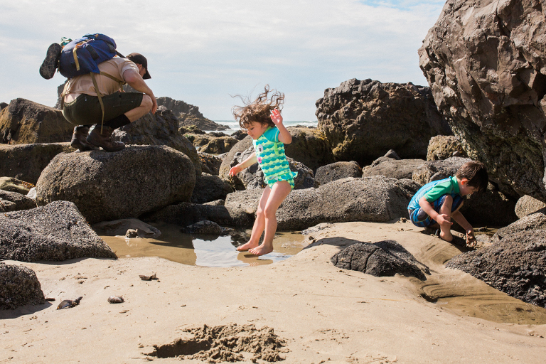 girl jumps in puddle at beach - Documentary Family Photography