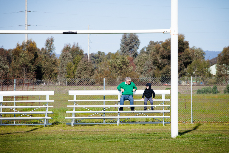 adult and child sitting in bleachers - Documentary Family Photography