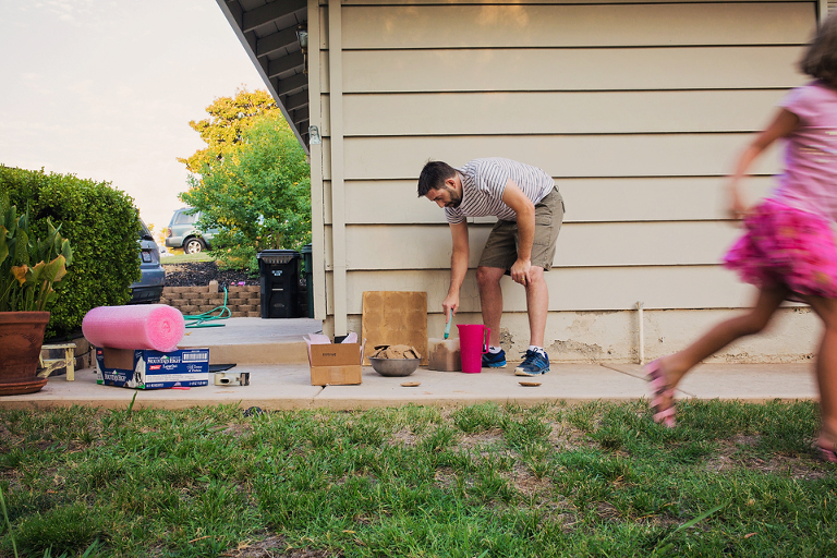father cleaning yard while child runs - Documentary Family Photography