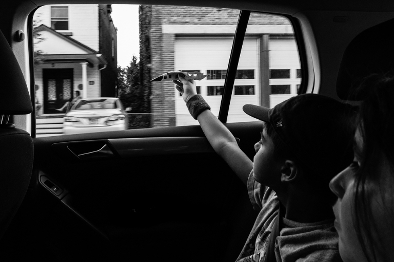 child flies toy plane out car window - Documentary Family Photography