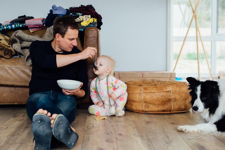 father feeding baby on floor - Documentary Family Photography