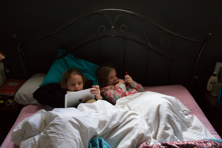 girls on tablet in bed - Documentary Family Photogarphy