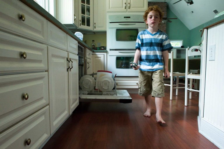Boy walks through kitchen making sour face - Documentary Family Photogarphy