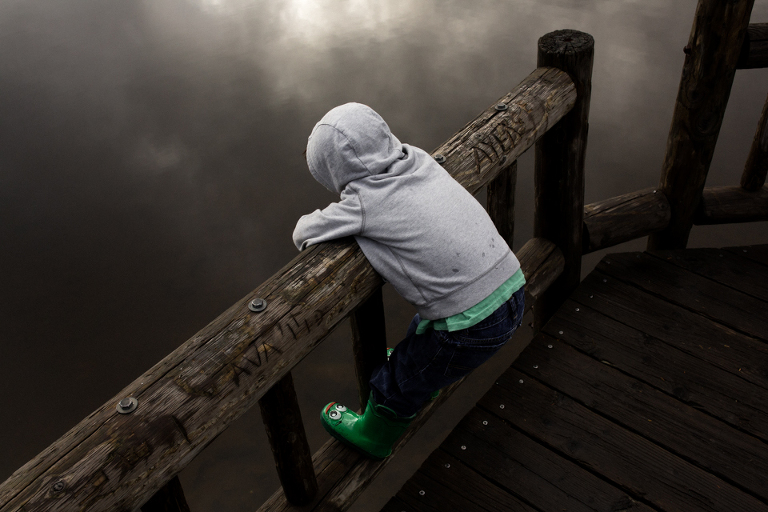 boy stands on bridge and gazes at water - Documentary Family Photography