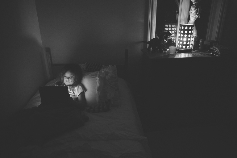 girl working on laptop in dark room - Documentary Family Photography