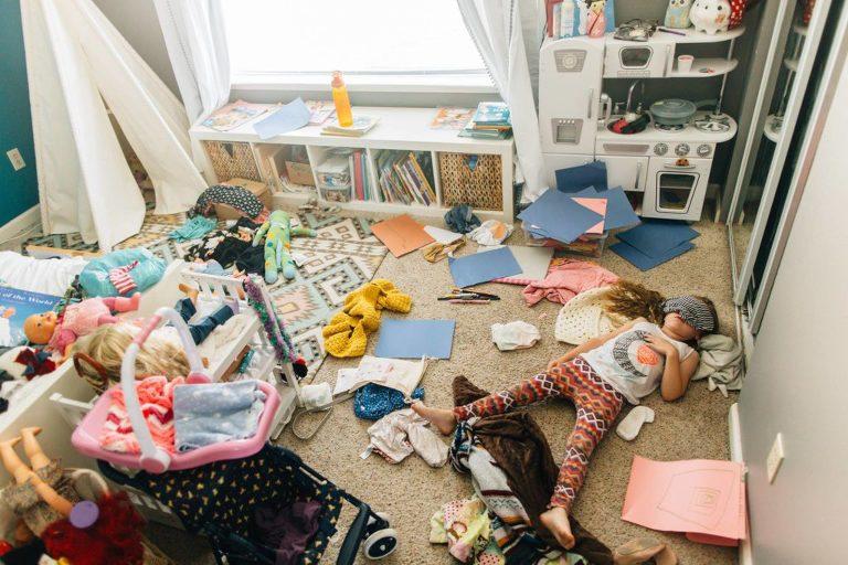 girl asleep on cluttered floor - Documentary Family Photography