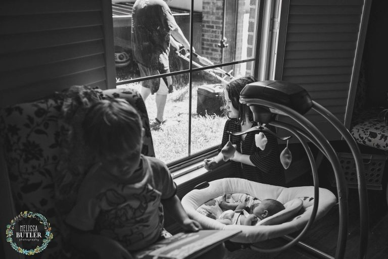 baby watches man mow lawn out window - Documentary Family Photography