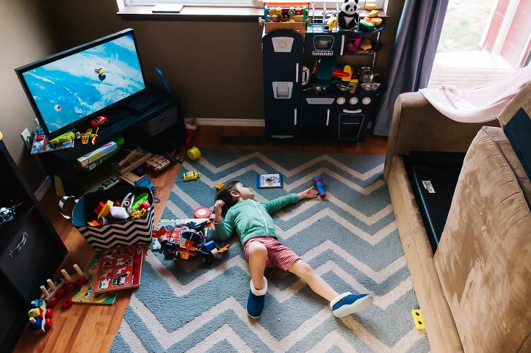 boy sprawls on floor amidst toys - Documentary Family Photography