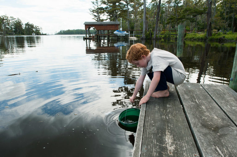 boy pulls up bucket from dock - Documentary Family Photography