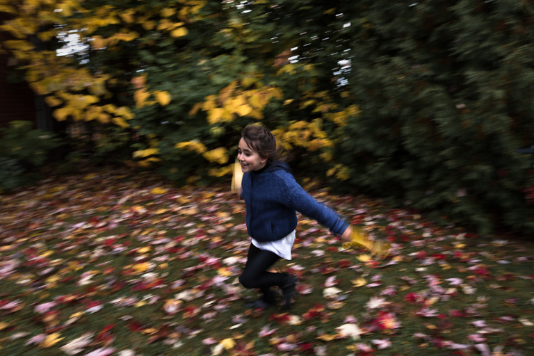 girl runs with leaves - Documentary Family Photography