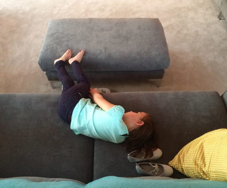 girl lays on couch - Documentary Family Photography