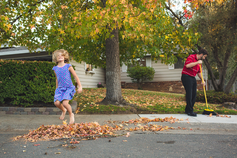 girl jumps in leaf pile - Documentary Family Photography