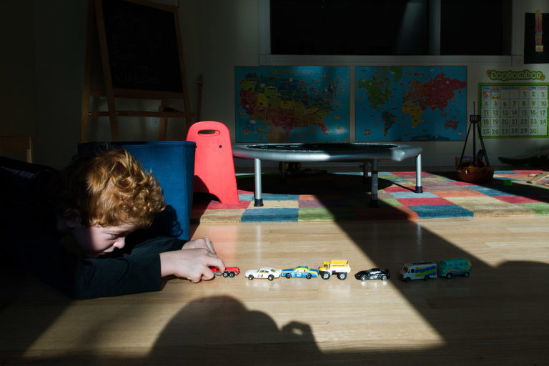 boy lines up toy cars - Documentary Family Photography