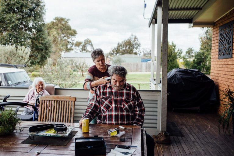 older woman gives older man haircut outside - Documentary Family Photography