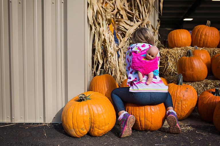 girl sits on pumpkin - Documentary Family Photography
