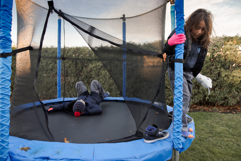 kids in jackets on trampoline - Documentary Family Photography