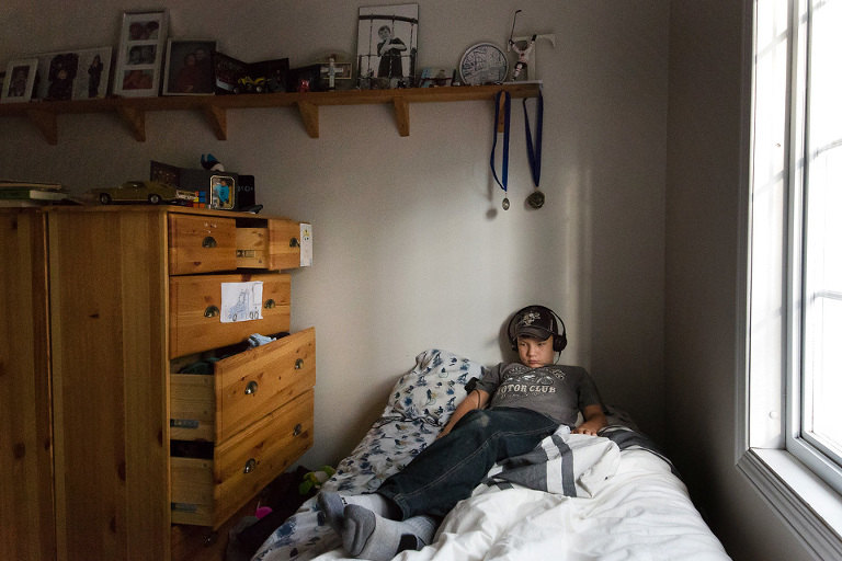 boy on bed with headphones - Documentary Family Photography