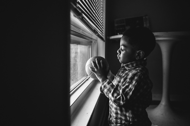 boy with ball at window - documentary family photography