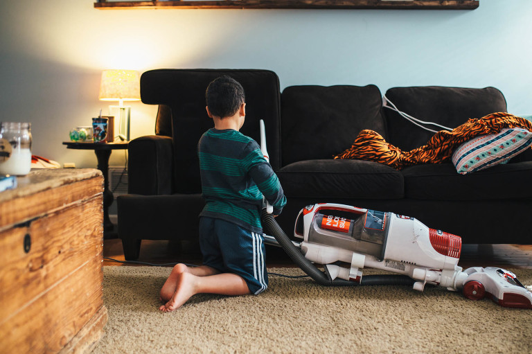 Boy vacuums couch - documentary family photography