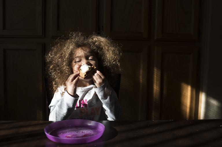girl eat cupcake in spot of sunlight - documentary family photography