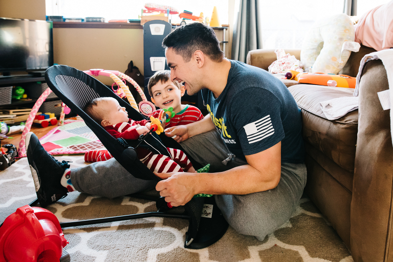 father plays with baby and son - documentary family photography