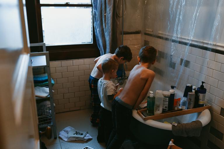Kids huddle around bathtub - documentary family photography