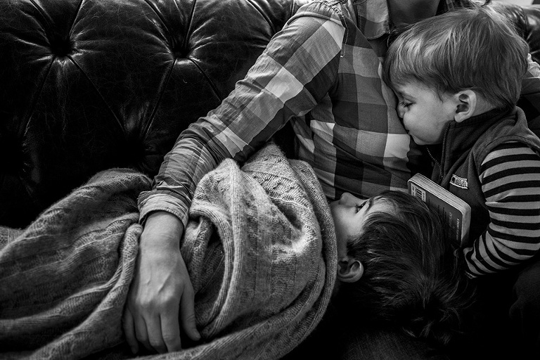 Family snuggles on couch