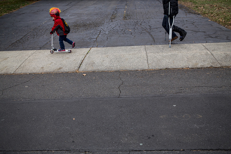 kid on scooter followed by parent on crutches