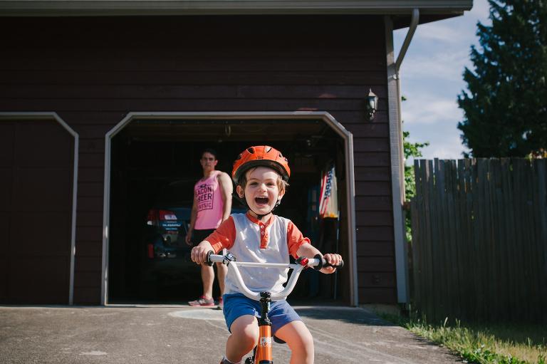 boy rides bike in driveway