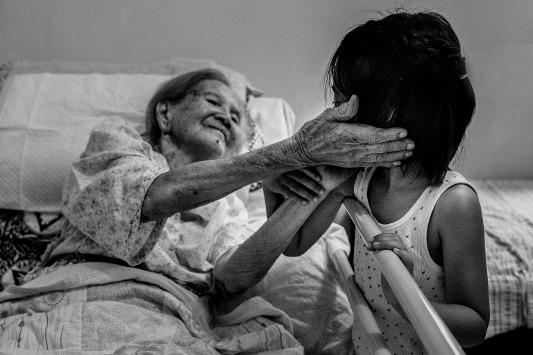 Elderly woman smiling at her great-granddaughter