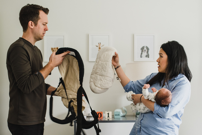 confused new parents with new baby and baby carrier
