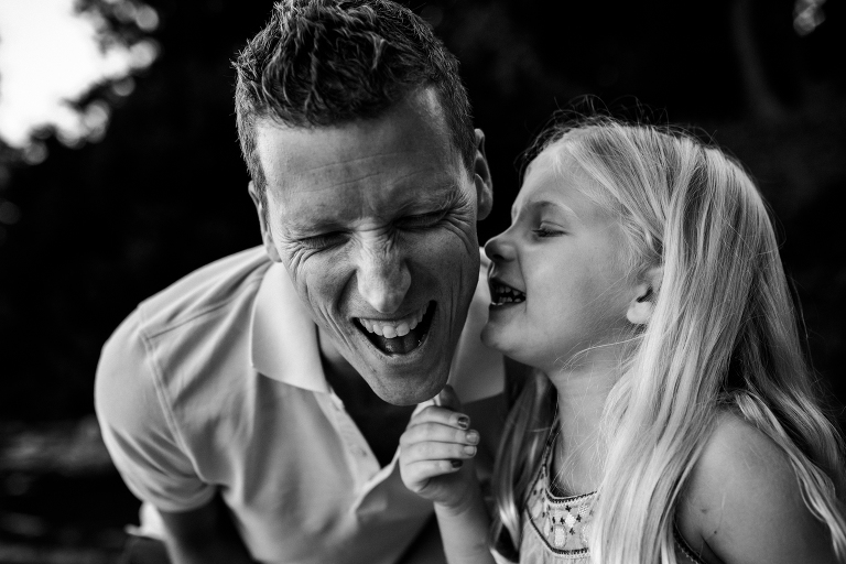 Father anticipating a kiss on the cheek from his daughter