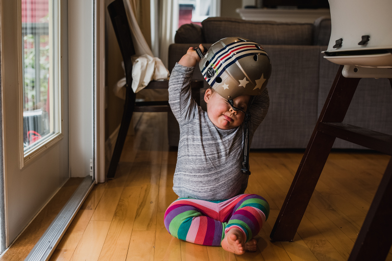 Toddler trying to remove a helmet off her head