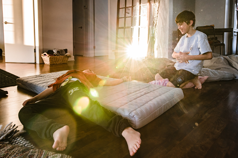 kids play on air mattress in sunlight - Documentary Family Photography