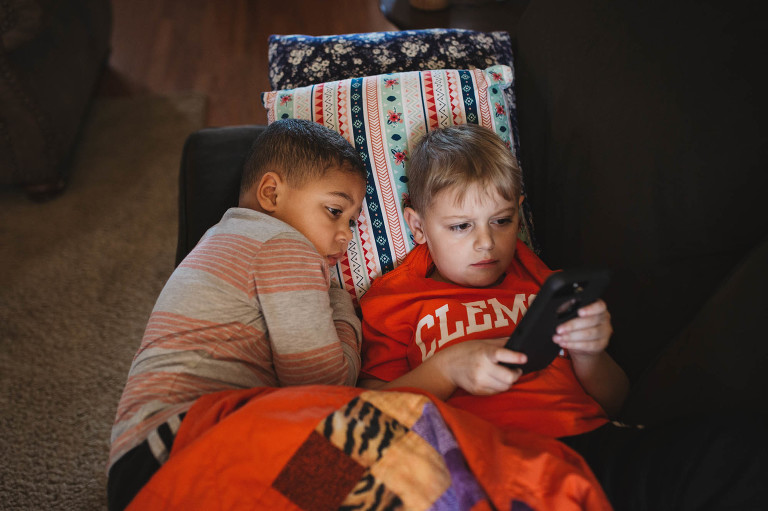 boys look at phone together - Documentary Family Photography