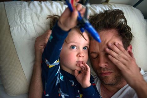 boy snuggles with tired dad - Documentary Family Photography