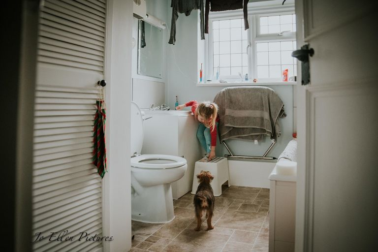girl with dog in bathroom - Documentary Family Photography