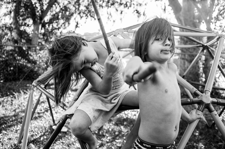 kids play on swing and play with sticks