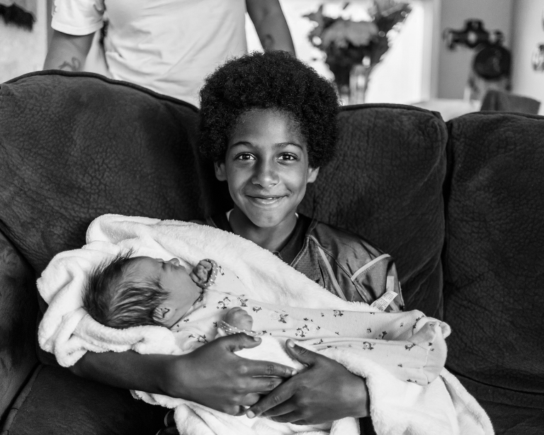 boy holds new baby