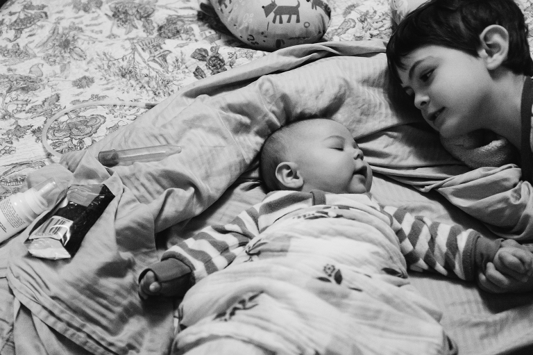 boy on bed with baby - Documentary Family Photography