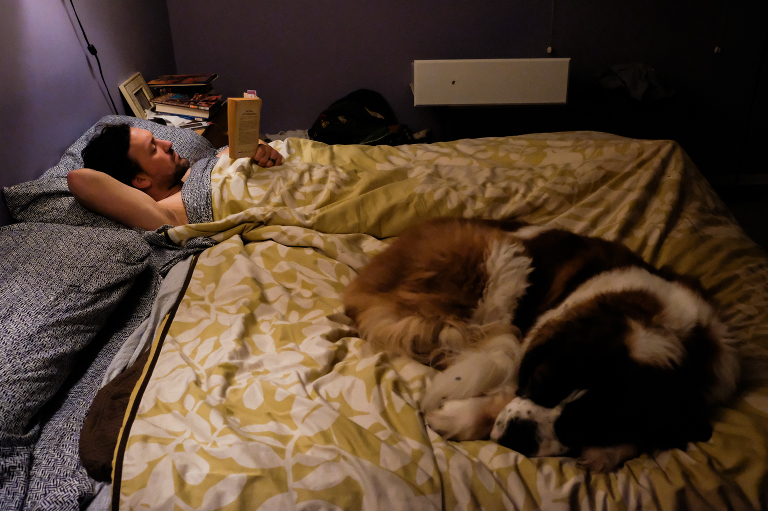 man reading in bed with dog - Documentary Family Photography