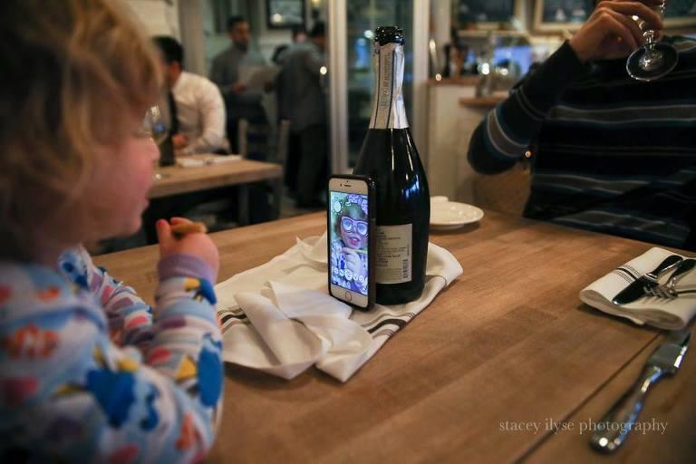 kid plays on phone - Documentary Family Photography