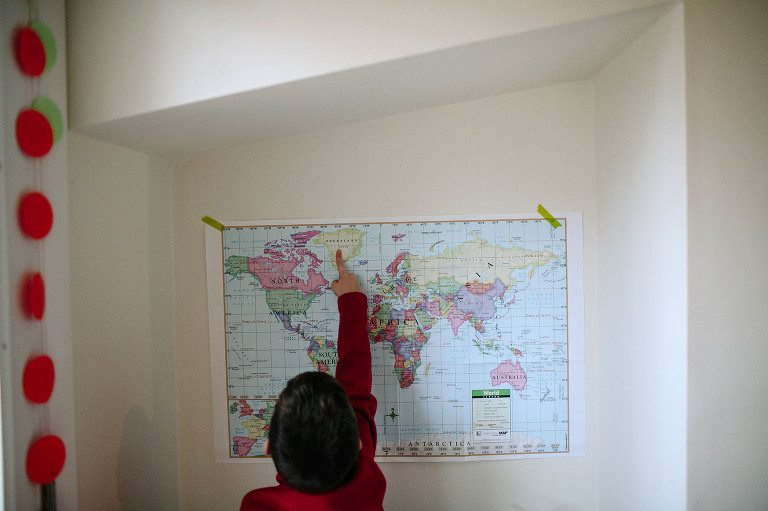 child points at spot on map - documentary family photography
