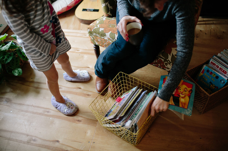 mother reaches for books while holding coffee - documentary family photography