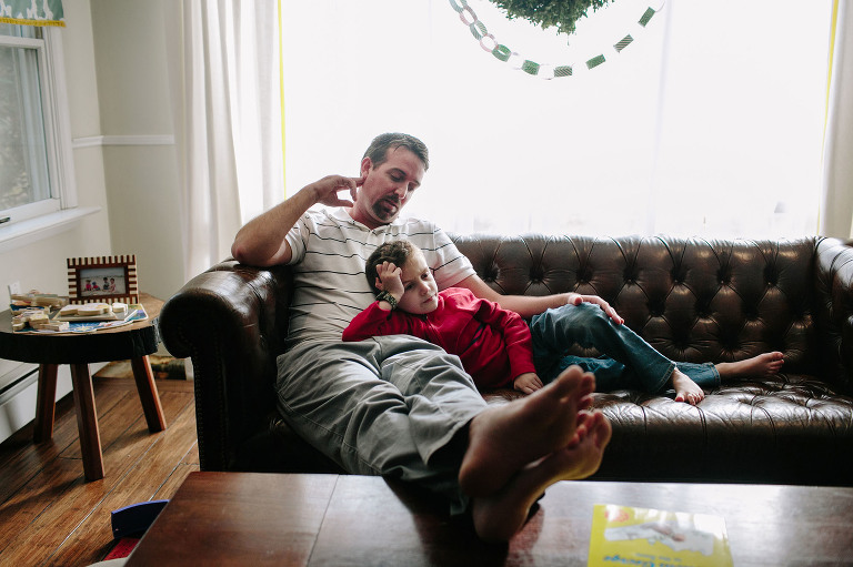 father and son on couch- documentary family photography