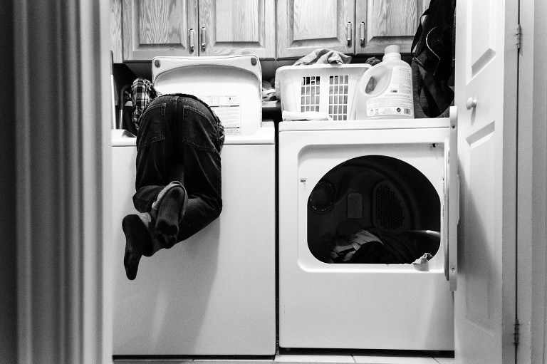 kid diving into washing machine - Documentary Family Photography